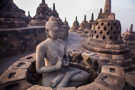 Buddha statue in Buddist temple of Borobudur in the morning. Yogyakarta. Java, Indonesia