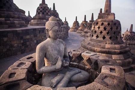 Buddha statue in Buddist temple of Borobudur in the morning. Yogyakarta. Java, Indonesia