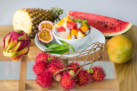 Fresh organic tropical fruits on the table and bowl of salad