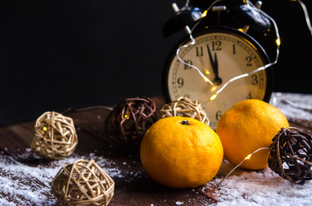 Mandarins close-up on a natural wooden surface against a background of vintage clock and surrounded by wicker balls. Stock Photo