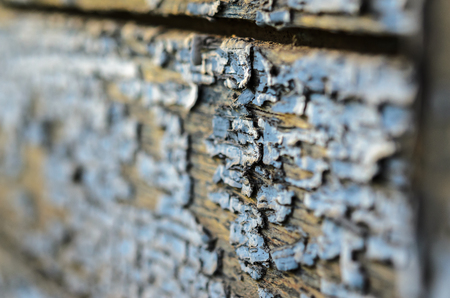 Texture of an old wooden board with peeling paint. Peeling paint close-up.