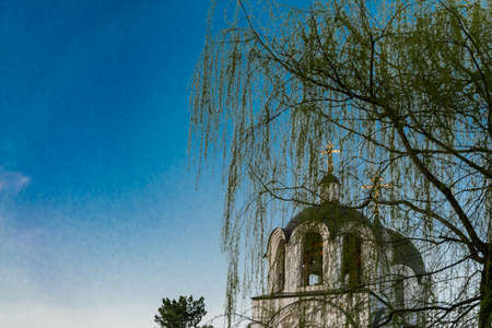 christian church against blue sky and willow branches through willow branches