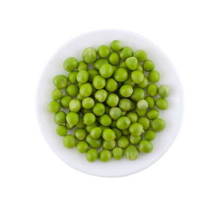 Piastra con piselli verdi su sfondo bianco. Archivio Fotografico