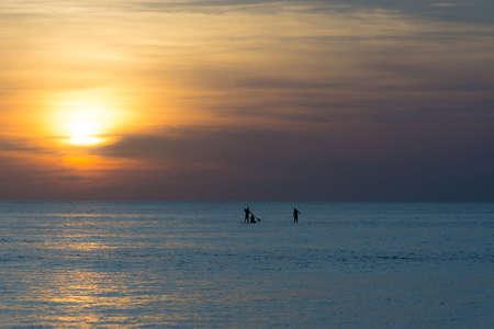 boarders: Three paddle boarders watching beautiful sunset Stock Photo