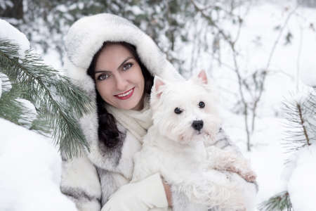 Pretty woman holding a dog in winter park Stock Photo