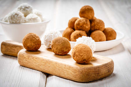 white and dark chocolate truffles or energy protein balls made with dry dates, walnuts, raisins, covered by cocoa powder