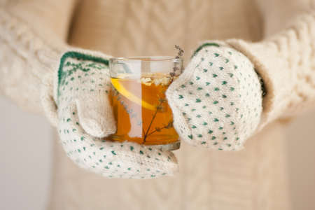 Hands in knitted mittens holding a cup of herbal tea with lemon on a cold day Stock Photo