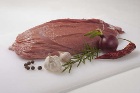 Fresh elk meat on a cutting board  Raw game meat  Rosemary, garlic, red onion, pepper and chilli