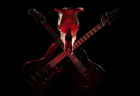 Rock band symbol - crossed electric guitars and skull on a black background  Stock Photo