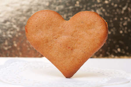 heart-shaped gingerbread cookie close-up on a golden background photo