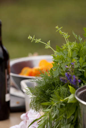 Close up of herb bouquet in the foreground; a bottle of wine and salad bowl with the chopped carrots in the background. Shallow depth of field. Focused on dill. Stock Photo