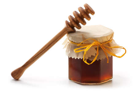 Honey Jar with wooden dipper isolated on white background photo