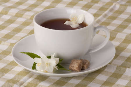 Cup of Jasmine tea and brown sugar cubes on a olive-green checkered tablecloth photo