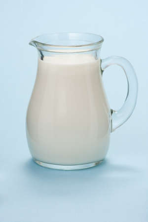 Glass jug with fresh milk isolated on a blue  azure  background