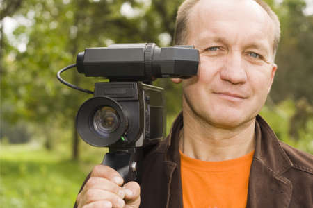 a grown man posing with a video camera on his shoulder  photo