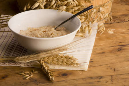 Oats, bowl of Oatmeal and ears of different sort of cereals on a wooden table
