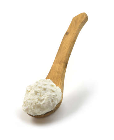 enrich: Cottage cheese in a wooden spoon, isolated on a white background  With clipping path  Stock Photo