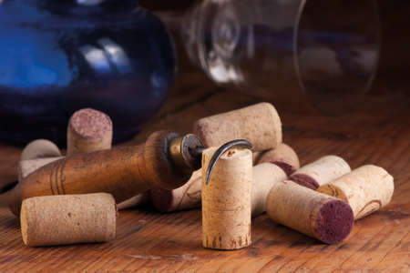 Old corkscrew, corks, blue bottle and overturned glass on a wooden table, still life  Selective focus Stock Photo - 18332305