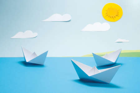 Origami paper boat floating in the sea on a paper sky background with white clouds and the sun  photo
