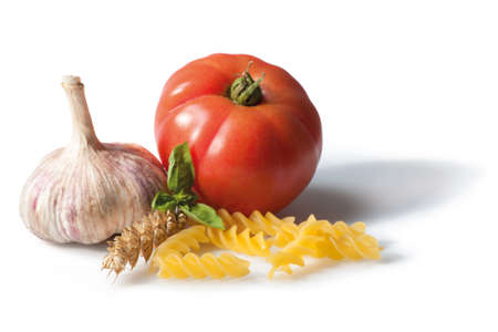 Still life. Composition with Fusilli pasta, basil, tomato garlic and wheat ears. Isolated on white. Focus on foreground. Stock Photo - 18332091
