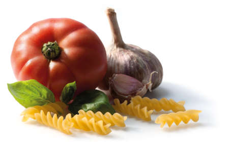 Still life. Composition with Fusilli pasta, basil, tomato and garlic. Isolated on white. Focus on foreground. Stock Photo - 18332130