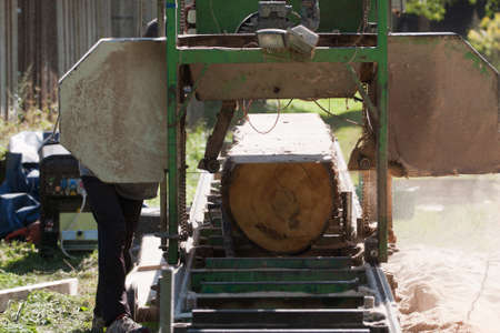 A man cutting timber on a portable sawmill. photo