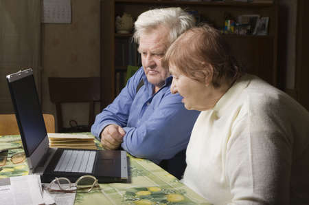Senior Couple in their Dining Room with a Laptop Computer Stock Photo