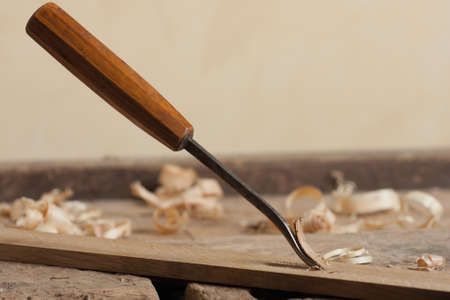 whittle: Chisel and wood shavings on a wooden workbench.