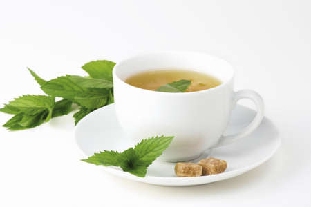 mint tea: A cup of mint tea with peppermint (mint) leaves and brown sugar on a white background.