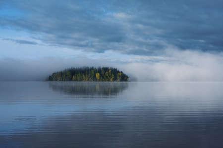 Small uninhabited island in the fog. photo