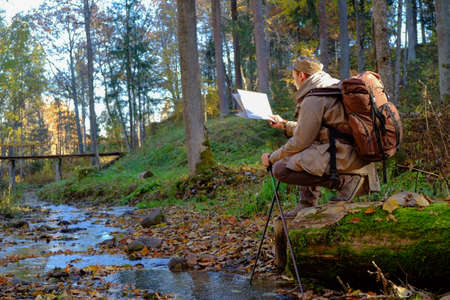 Young man traveler exploring the map in autumn forest. photo