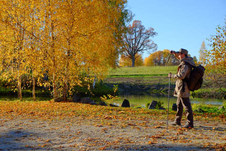 A young man walking along the lake. Golden autumn. photo