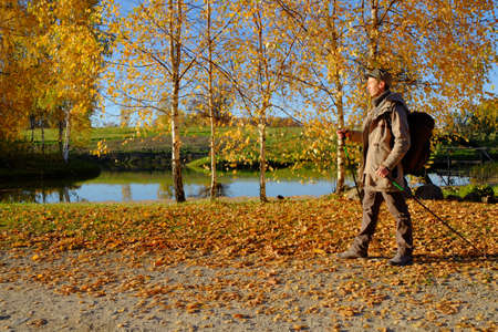 A young man walking along the lake. Golden autumn.