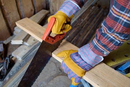 Carpenter cutting a board with a hand saw