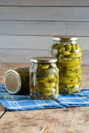 Three jars with pickled cucumbers on the wooden table. Close-up