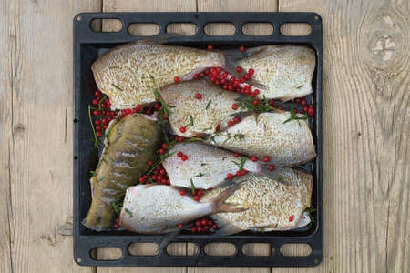 Fish Meat on a Black Tray on Top of a Rustic Wooden Table. Captured in High Angle View