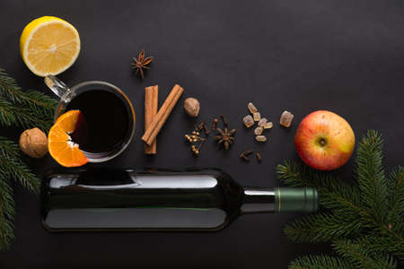 Christmas Mulled wine recipe ingredients on black. Bottle of wine, orange, apple, lemon, cinnamon sticks, anise, nutmeg, cloves and sugar from above. With text space