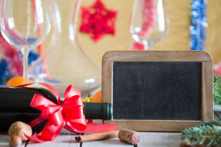 Bottle of wine and decorations next to empty blackboard for your text on wooden table. Christmas or New Years drink. Stock Photo