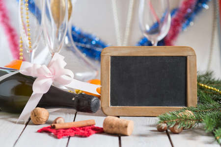 Bottle of champagne and decorations next to empty blackboard for your text on wooden table. Christmas or New Years drink. Stock Photo