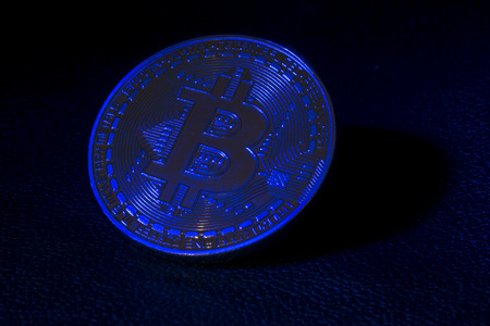 gold coin bitcoin on black leather in the rays of blue light.