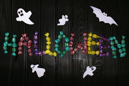 Halloween candy lettering on a black wooden background with figures of ghosts and a bat Stockfoto