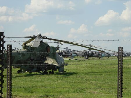 many Russian military helicopters are based in a Parking lot behind a barbed wire fence