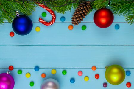 Christmas back,ground, green fir branches, red and blue, pink, yellow, ball, candies, cone, blue boards