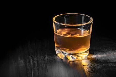 einzelnes Glas Cognac auf einem schwarzen Baum