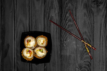 sushi rolls in a black plate on black boards top view