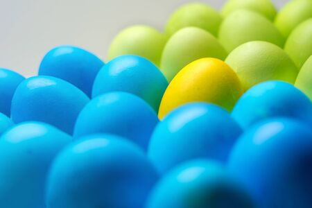 Easter colored eggs multicolor closeup of one of the yellow stands out Stockfoto