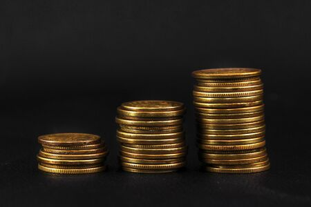 three stacks of coins on black leather