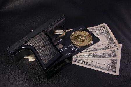 dollars money Bank card gold coin bitcoin black gun Stockfoto