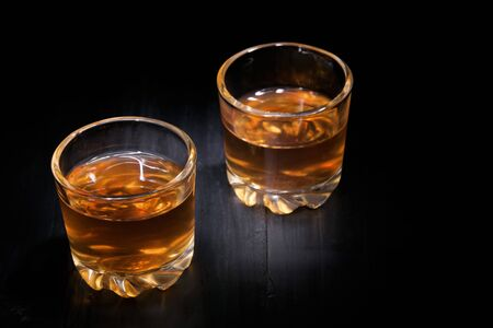 two glasses of cognac on a black tree