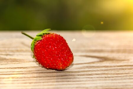 one strawberry on a wooden table with green bokeh